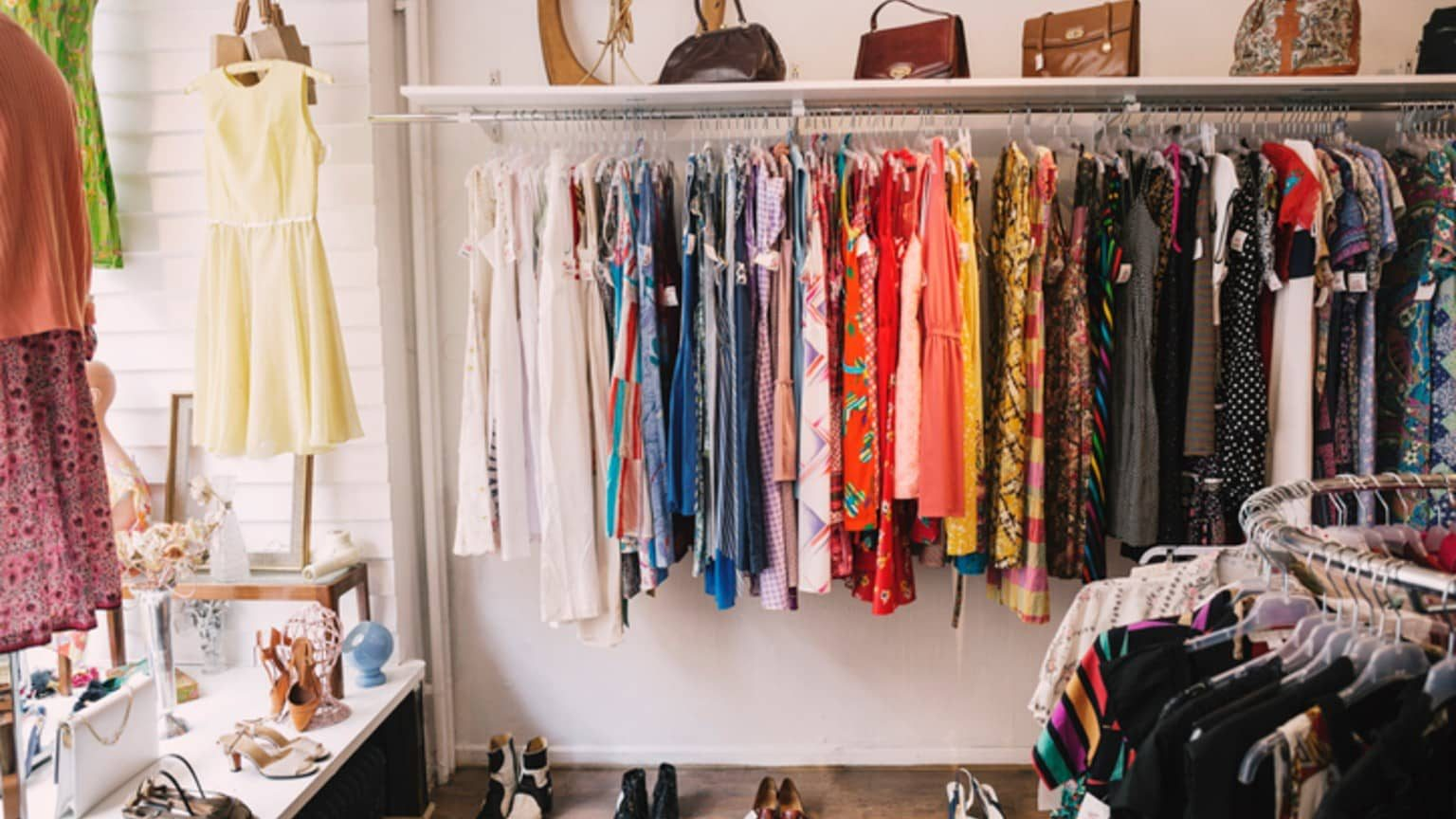 dresses hanging, purse and shoes in a thrift shop