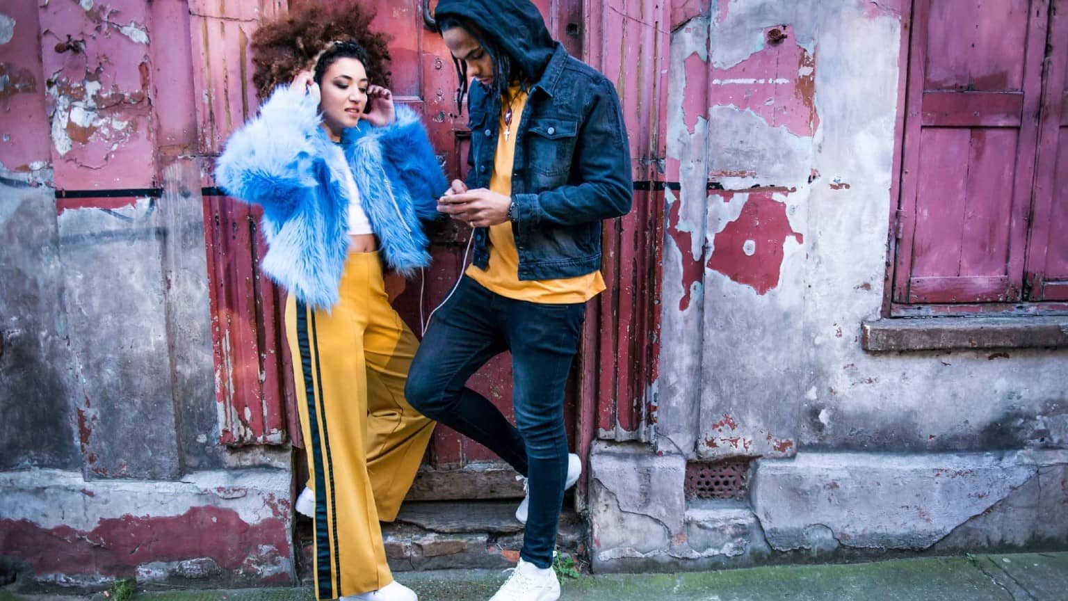two people standing leaned against a wall listening to headphones