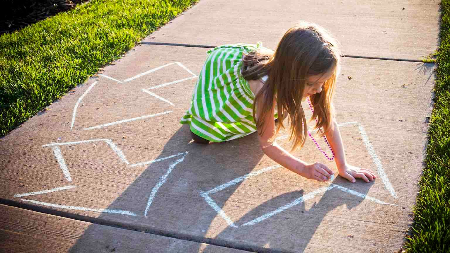 A young girl drawing a recycling symbol with chalk on the sidewalk outside.