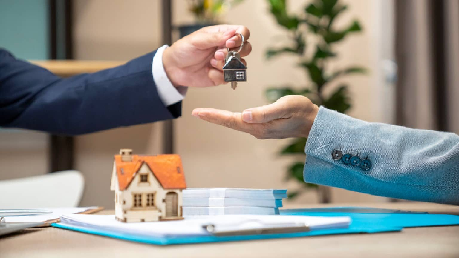 a person handing someone else keys to a home