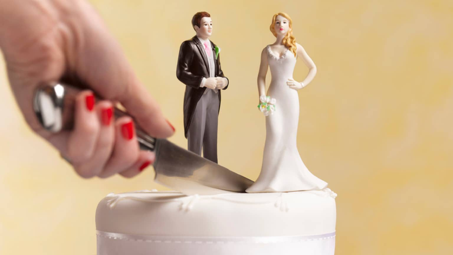 a wedding cake being cut in half between the man and woman topper signifying divorce