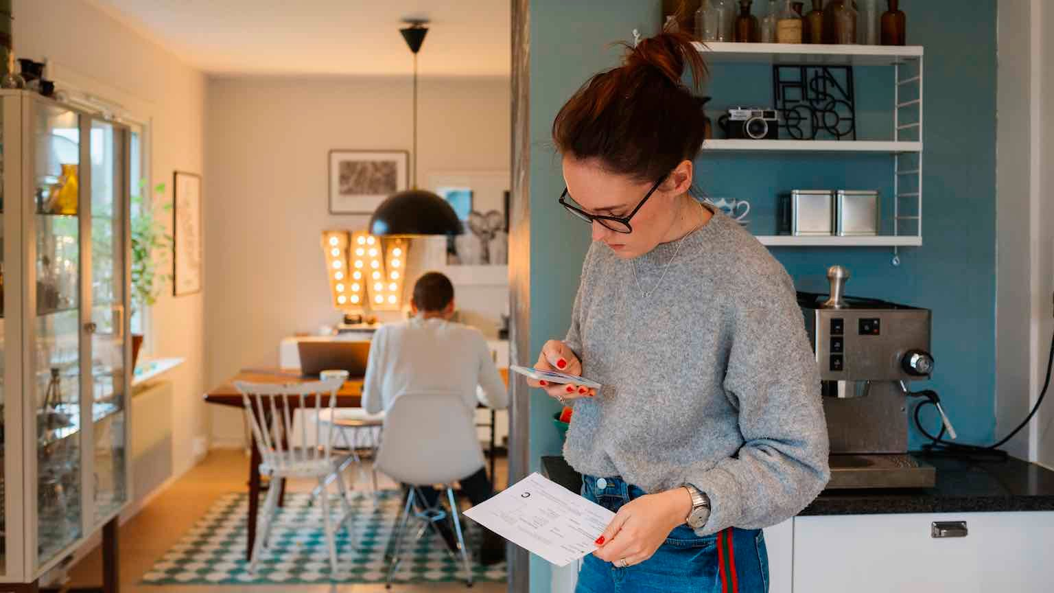 Woman paying bills in kitchen