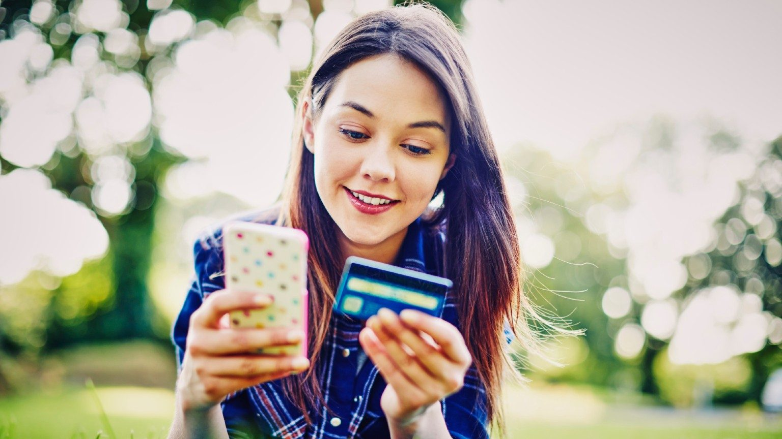 Young woman in park using bank card and phone.
