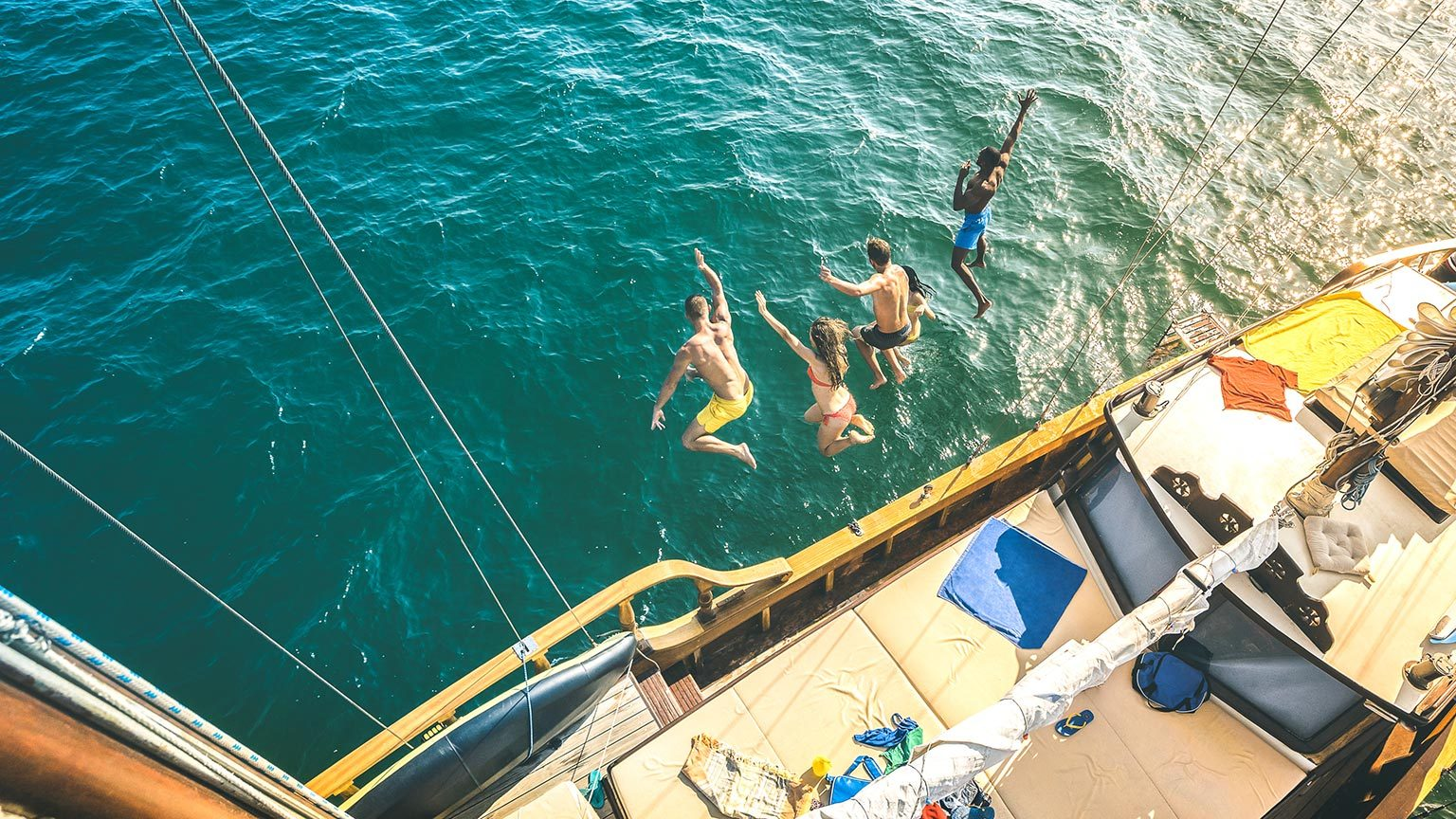 Group jumping off cruise desk into water