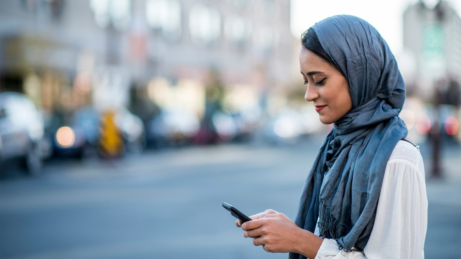 Lady in hijab looking at mobile phone
