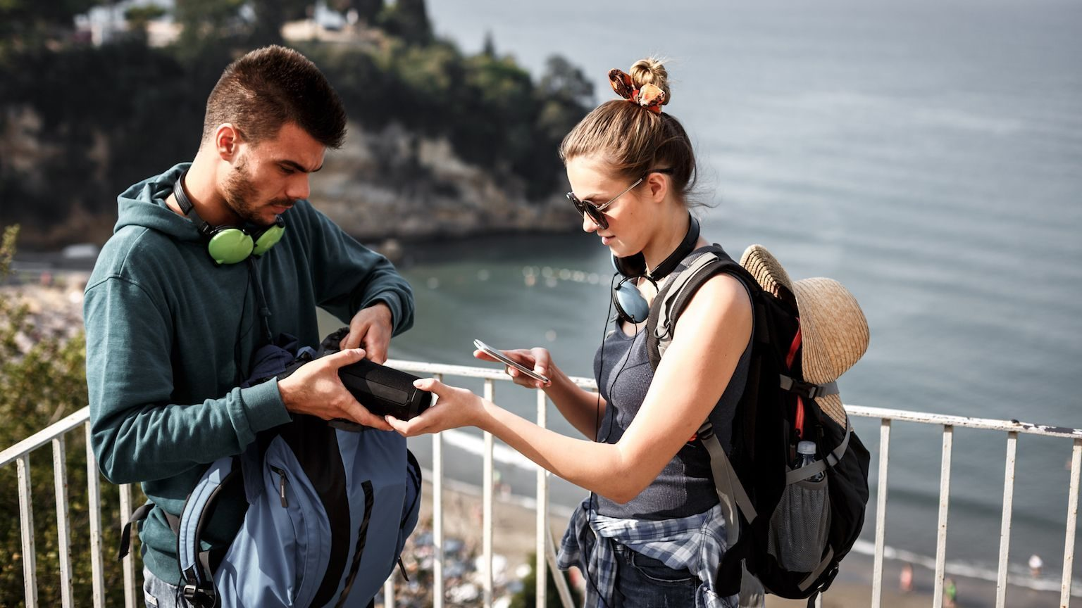 Young couple using a Bluetooth speaker on a hike