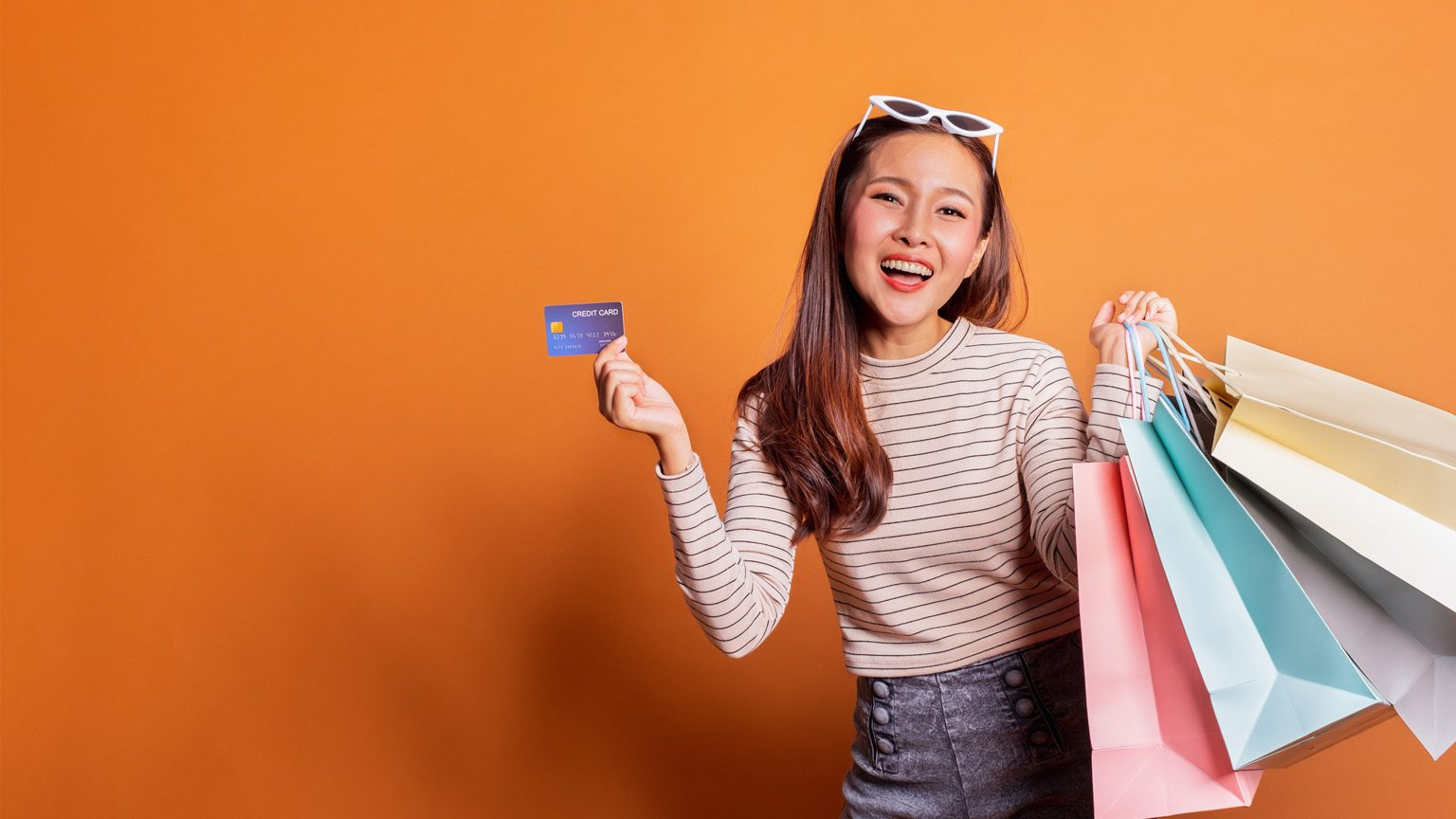 Lady holding a credit card and shopping bags