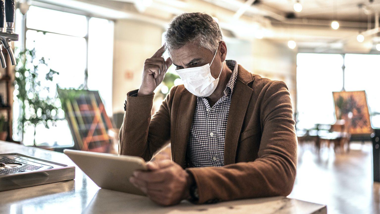 Homme avec masque de protection qui gère un compte bancaire en ligne