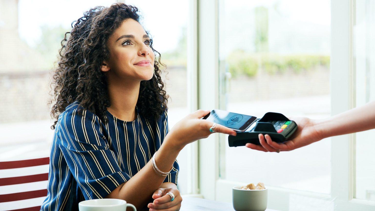 Une femme paie son café avec son smartphone et Google Pay