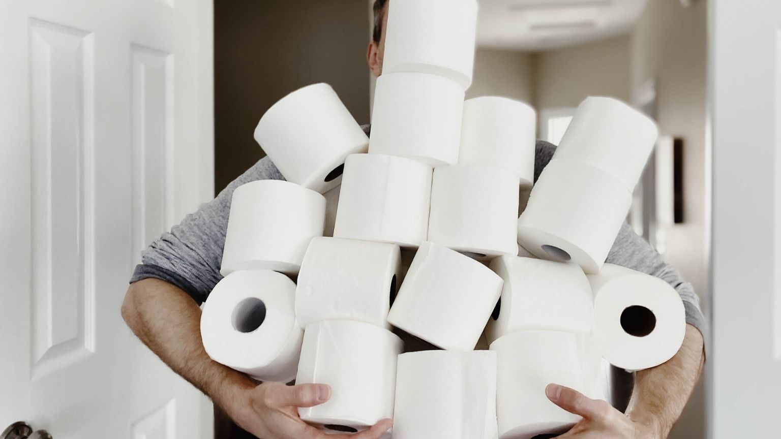 Man holding a pile of toilet paper rolls