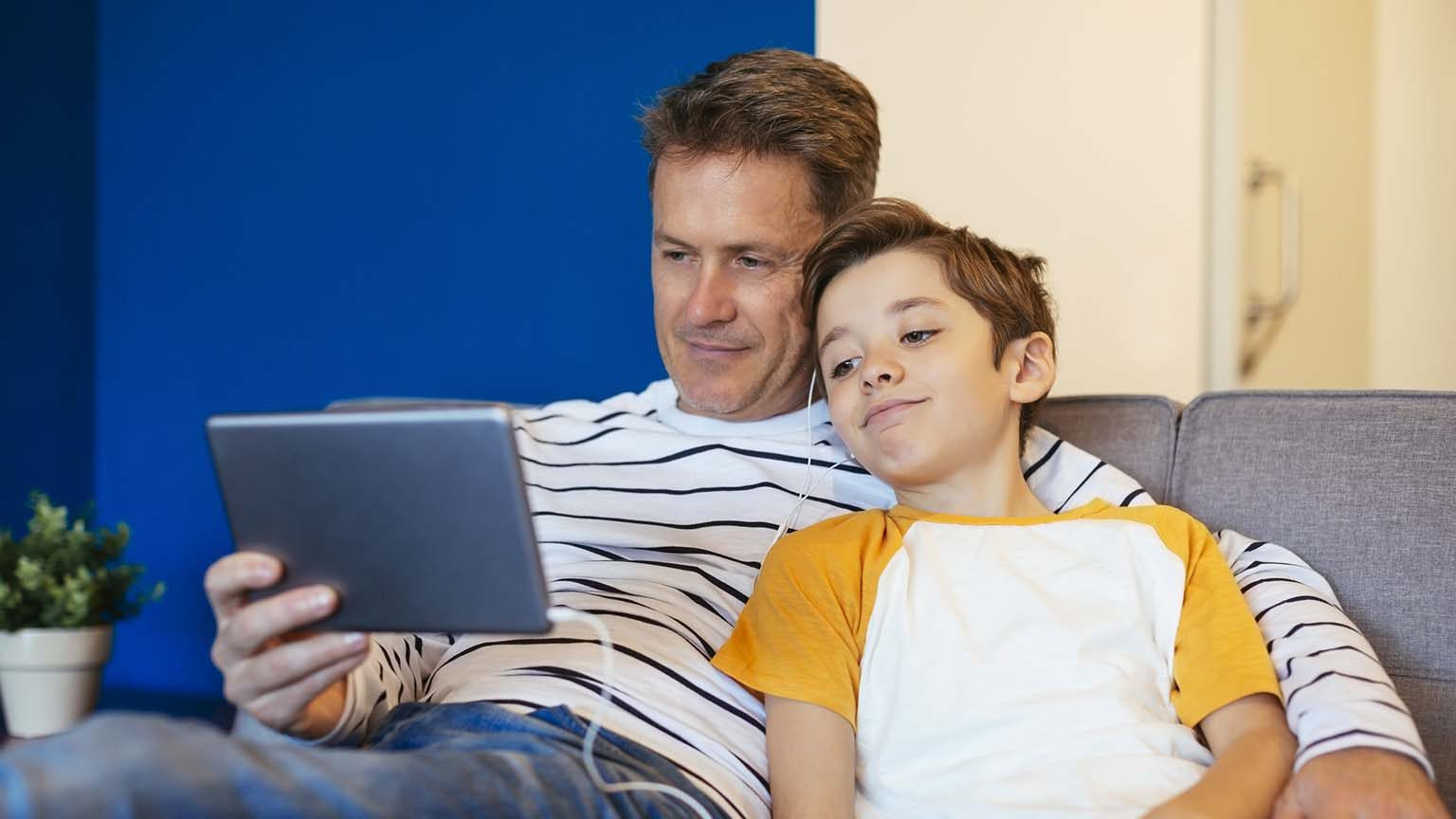 man and son watching ipad