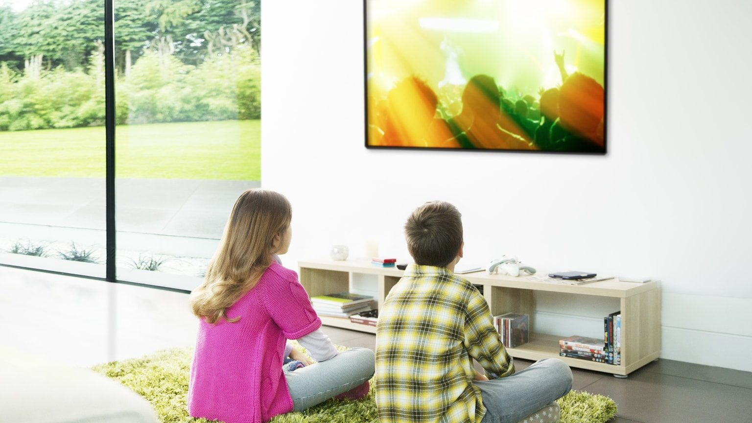 Children sitting in front of a flat screen TV