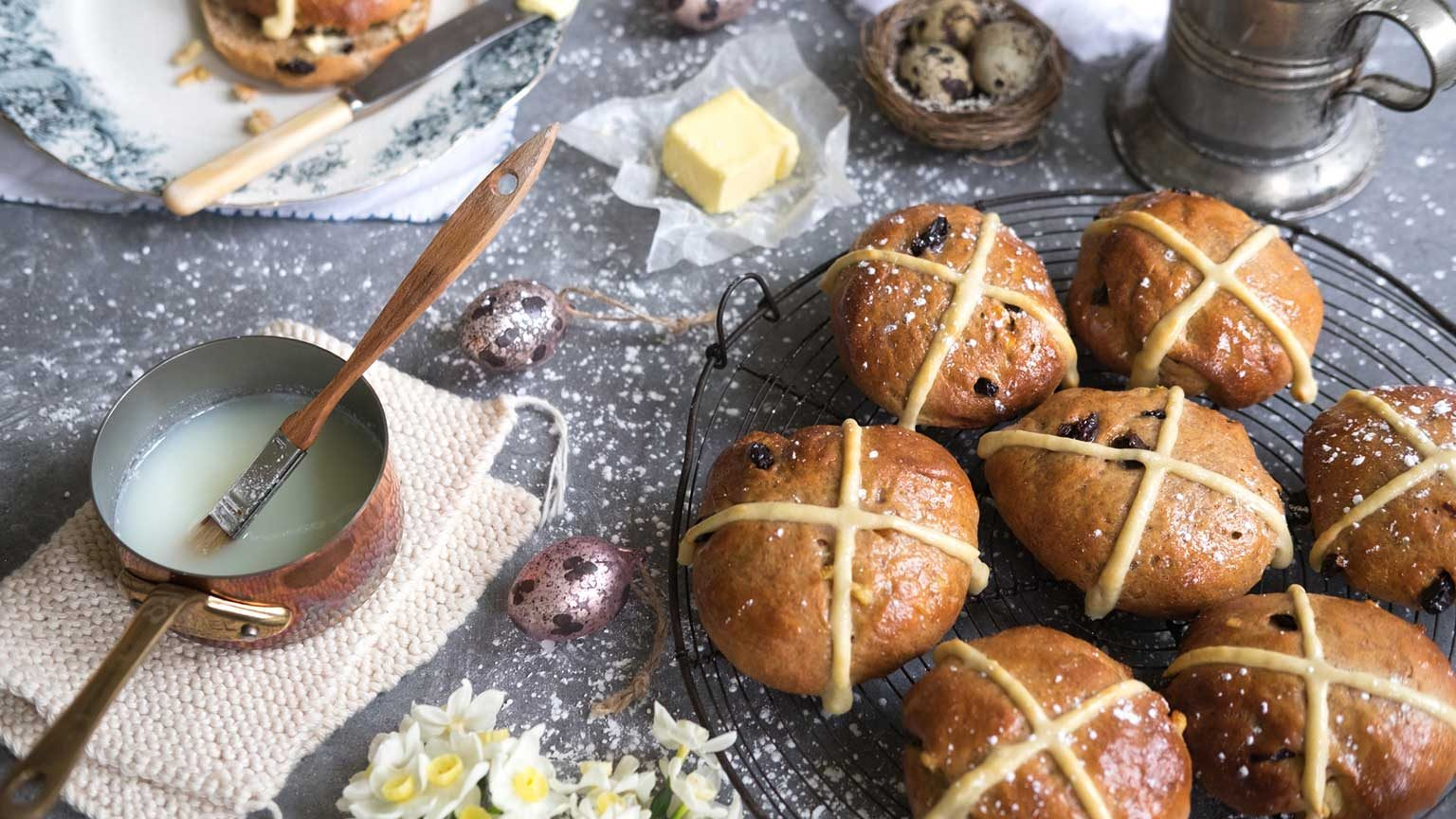 Cooking shot showing traditional hot cross buns being glazed with a sugar syrup.