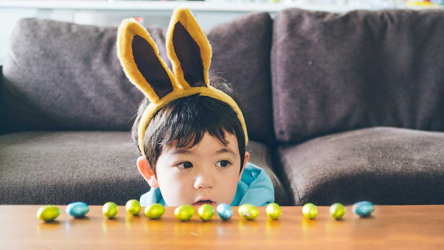 Young boy wearing rabbit eats looking at a line of easter eggs laid out on a table.