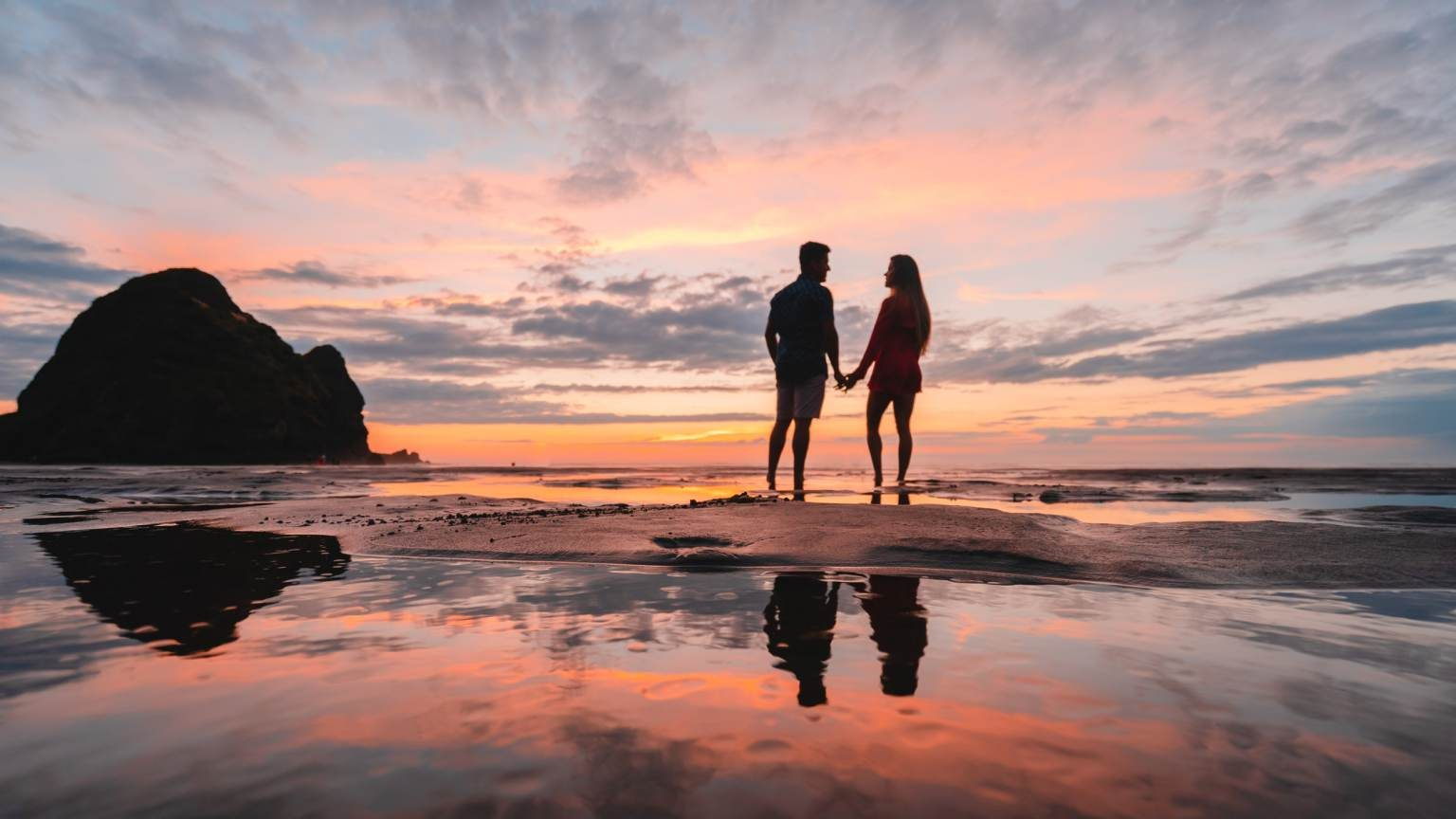 Couple at Piha beach holding hands and looking at each other.