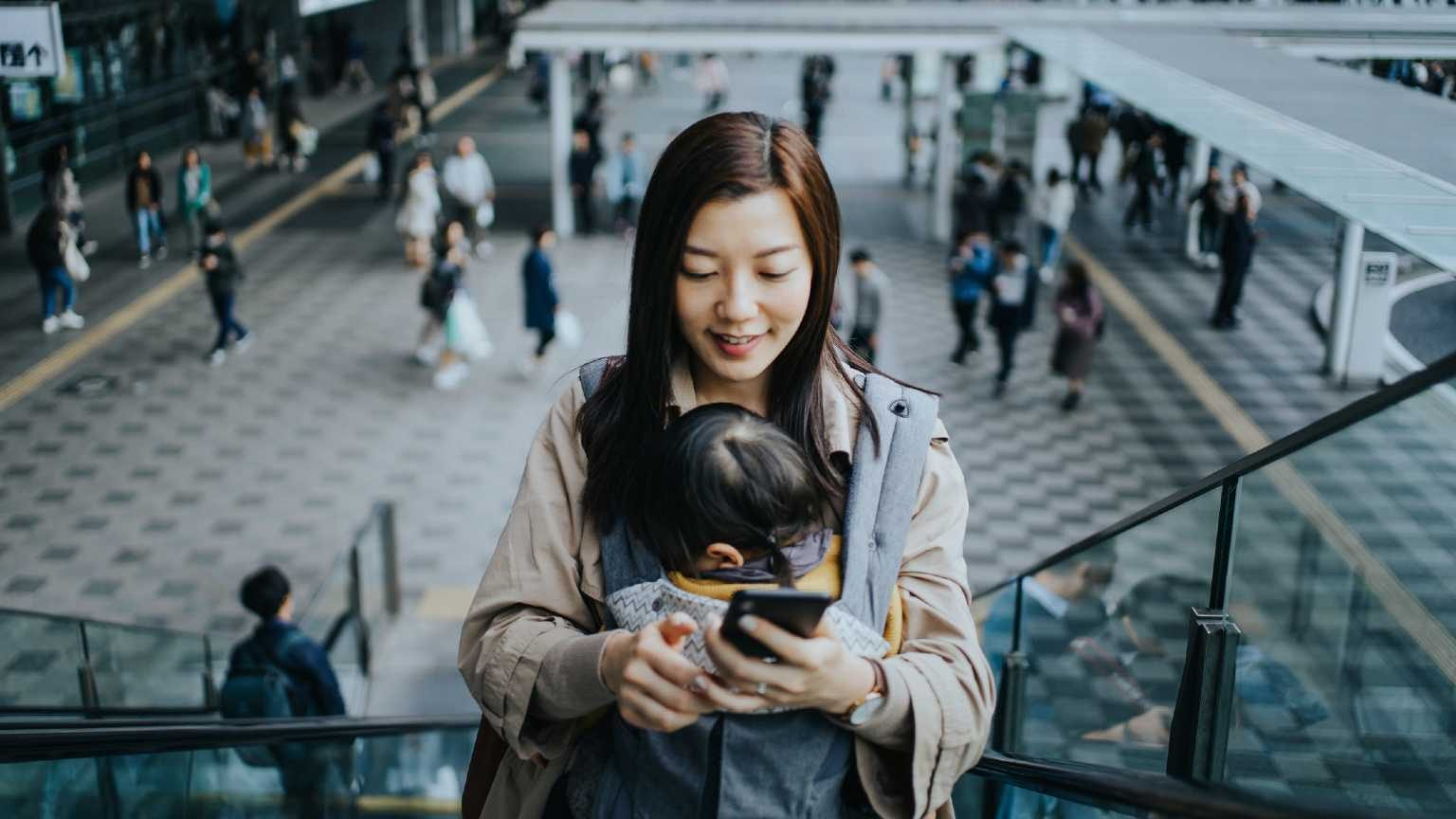 Woman on her phone with a baby