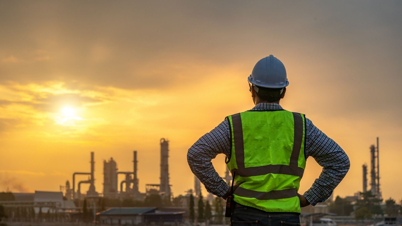 a working man looking at a gas refinery