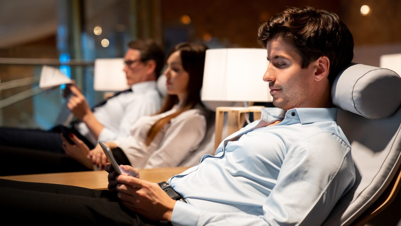 Traveling business man relaxing in a VIP lounge at the airport texting on their phone while waiting for his flight - travel concepts (Traveling business man relaxing in a VIP lounge at the airport texting on their phone while waiting for his flight -