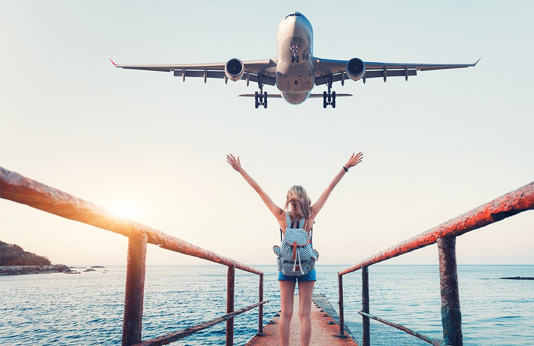 Girl waving at a plane as it flies overhead