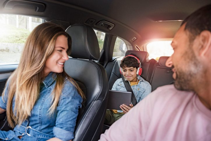 Family on a road trip with boy using tablet