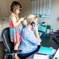 Middle Aged Women working from home in office whilst also looking after her young daugther.