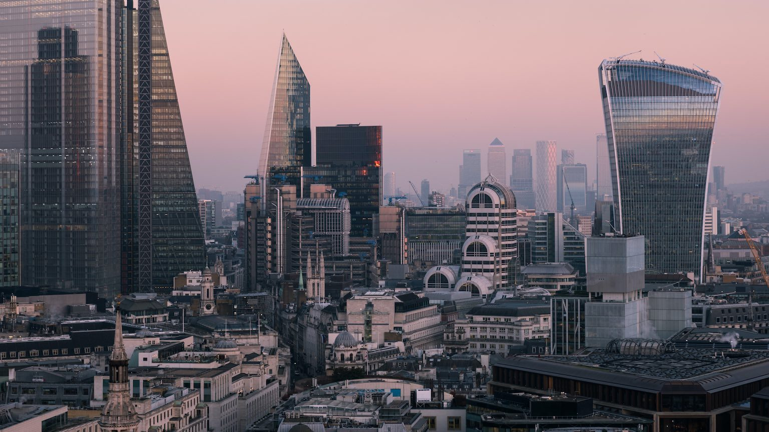 Elevated view of the City of London's illuminated financial district skyline at dusk.