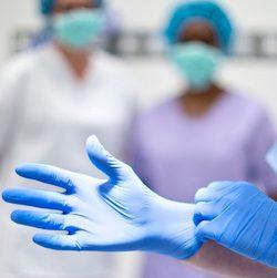 Surgeon putting on latex glove