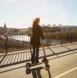 Full length of female commuter riding electric push scooter on bridge in city against sky