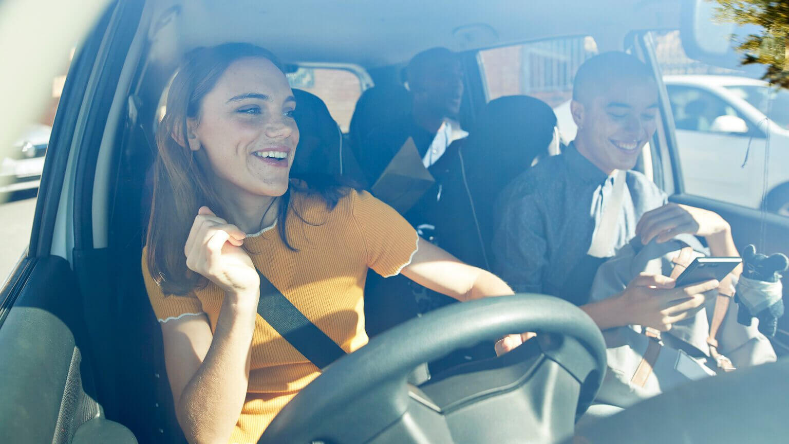 Young woman smiling and driving the car with her friends