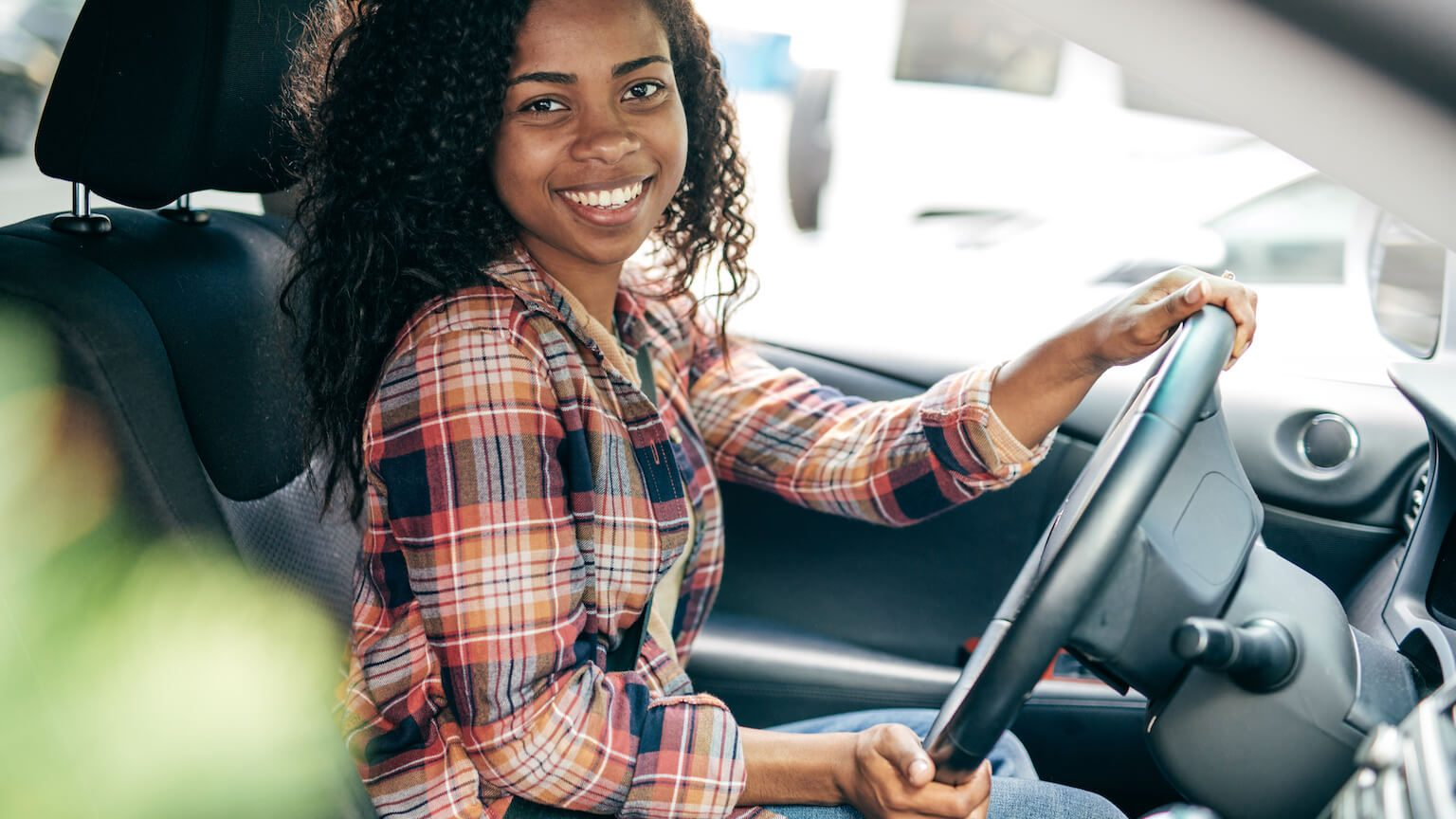 woman in chequered shirt smiling whilst driving
