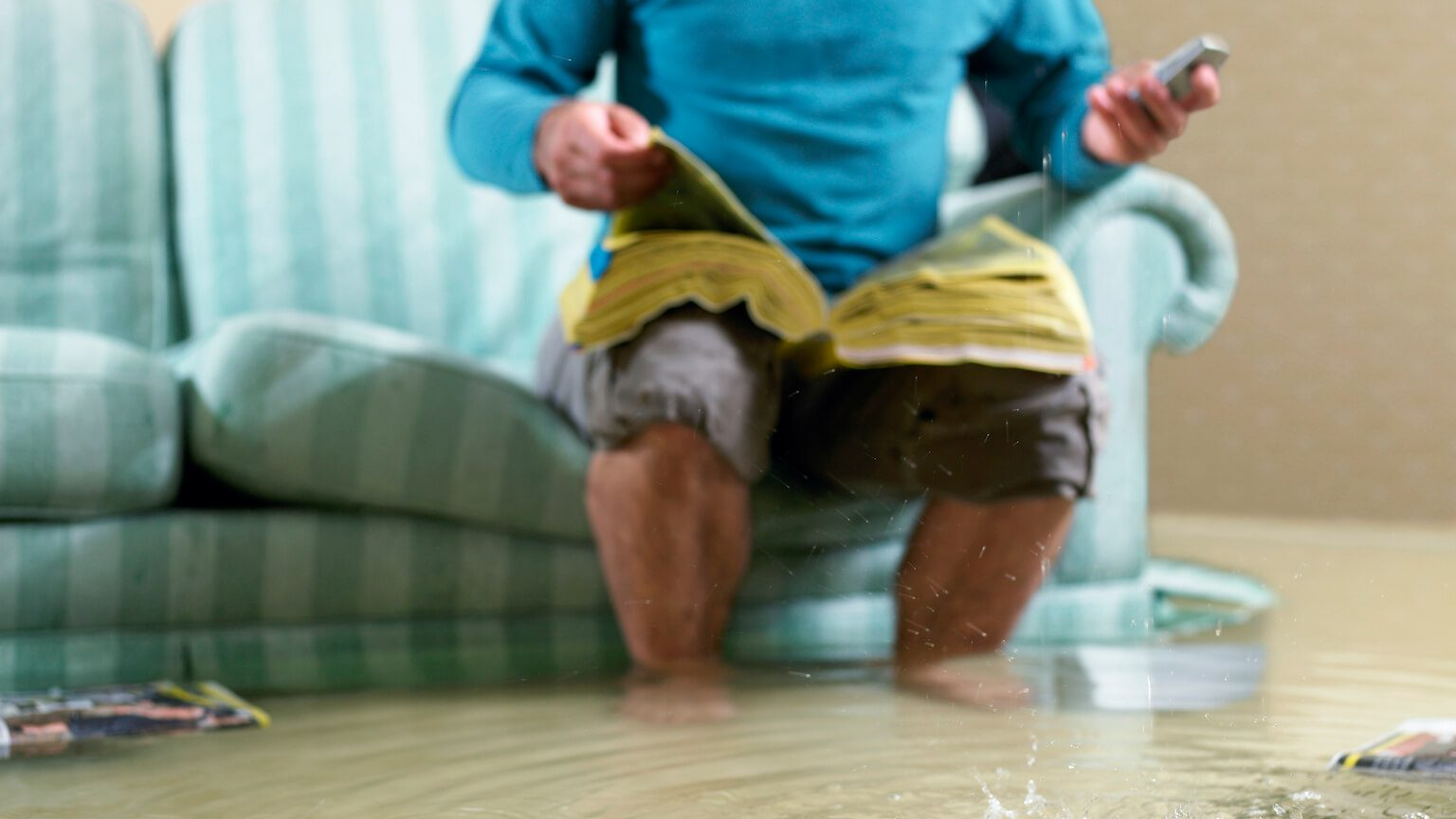 man looking through the yellow pages directory after a home emergency flooding