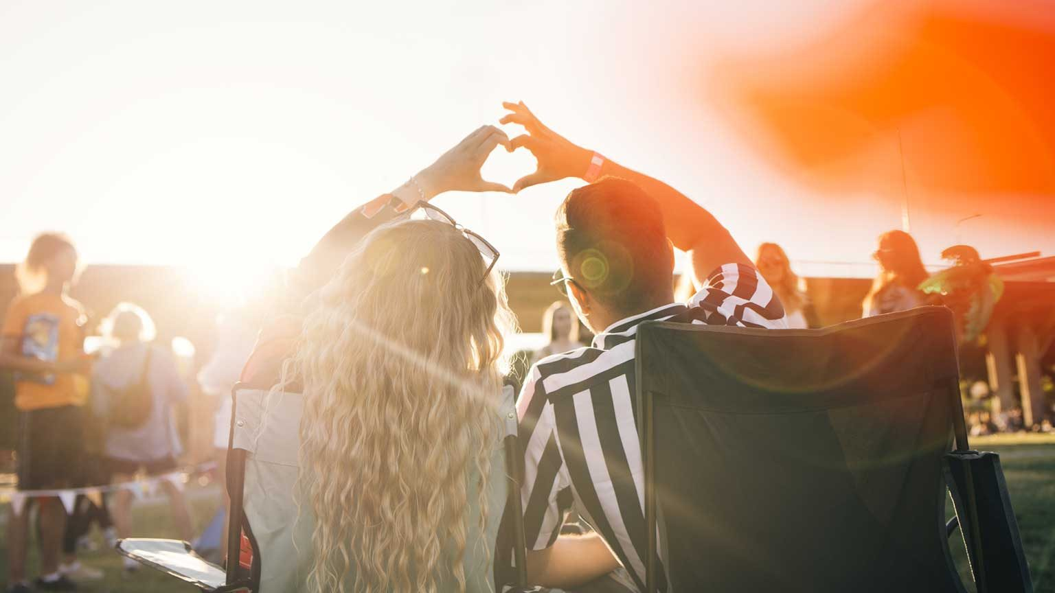 Couple at a festival holding hands in a love heart.