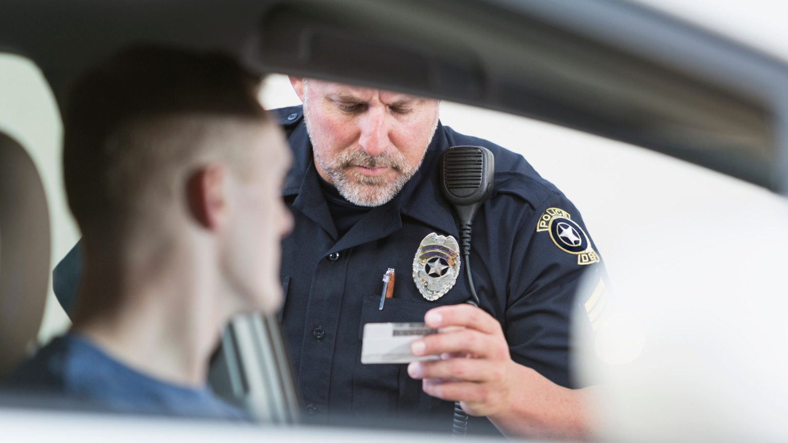 Cop looking at a man's drivers license through open car window