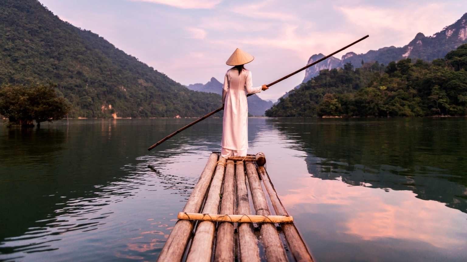 Asia, Vietnam, Hanoi, Vietnamese woman wearing traditional clothing, punting a bamboo raft across lake, at sunset