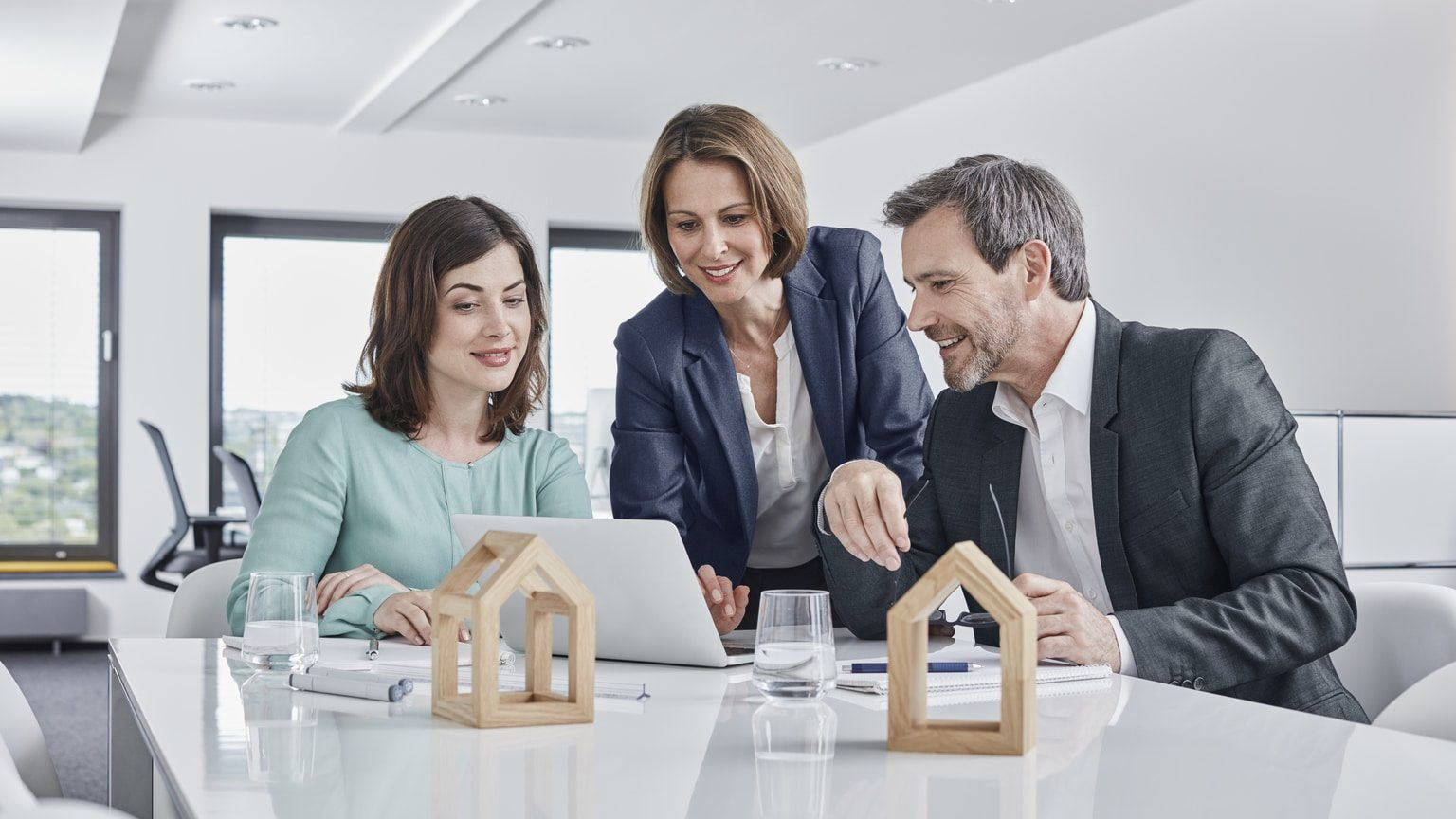 Couple looking over mortgage documents with real estate saleswoman