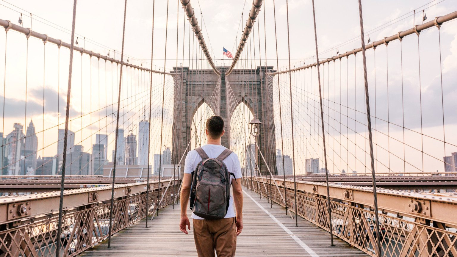 A young man with a backpack walking the Brooklyn bridge