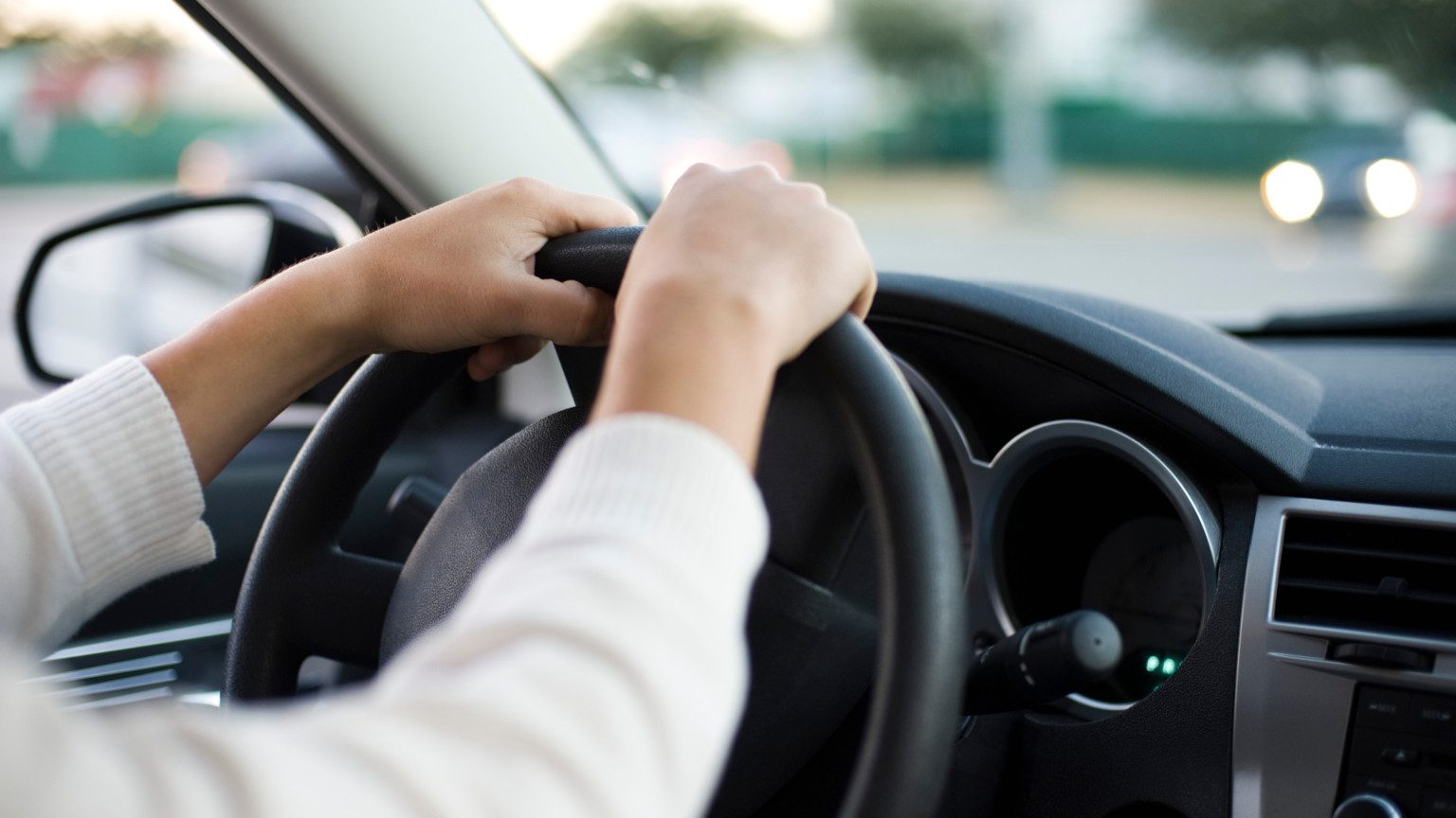 Close up of two hands on steering wheel of car while driving