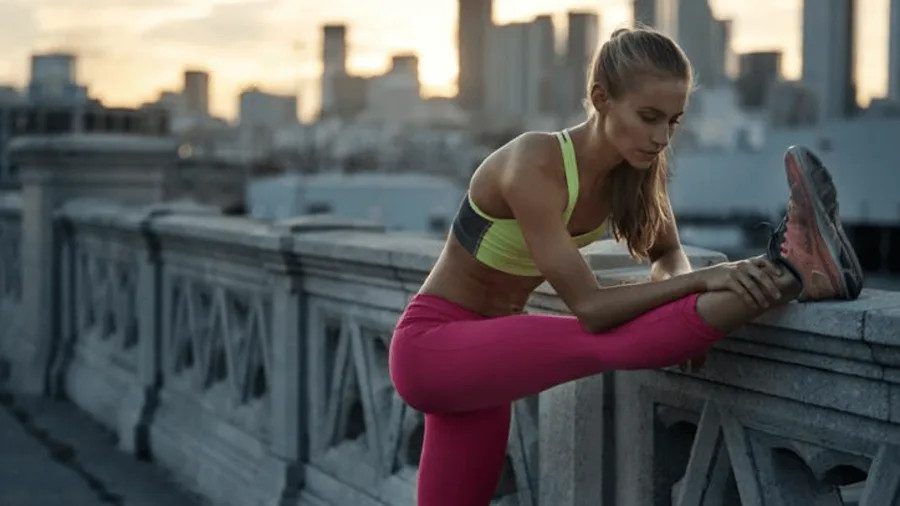 Woman stretching outside in exercise clothes
