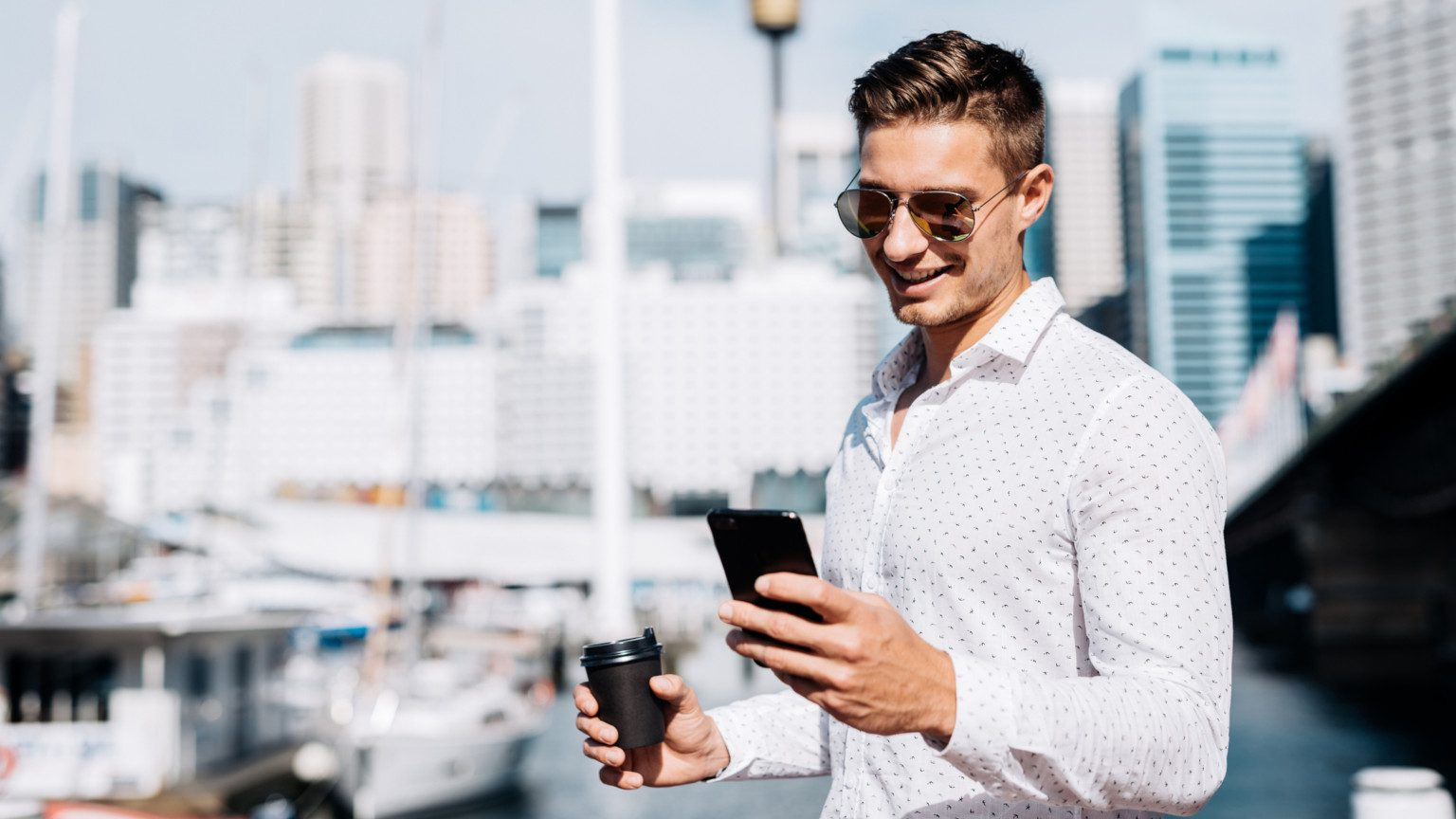 Young man with sunglasses standing outside in the sun with his phone and a coffee