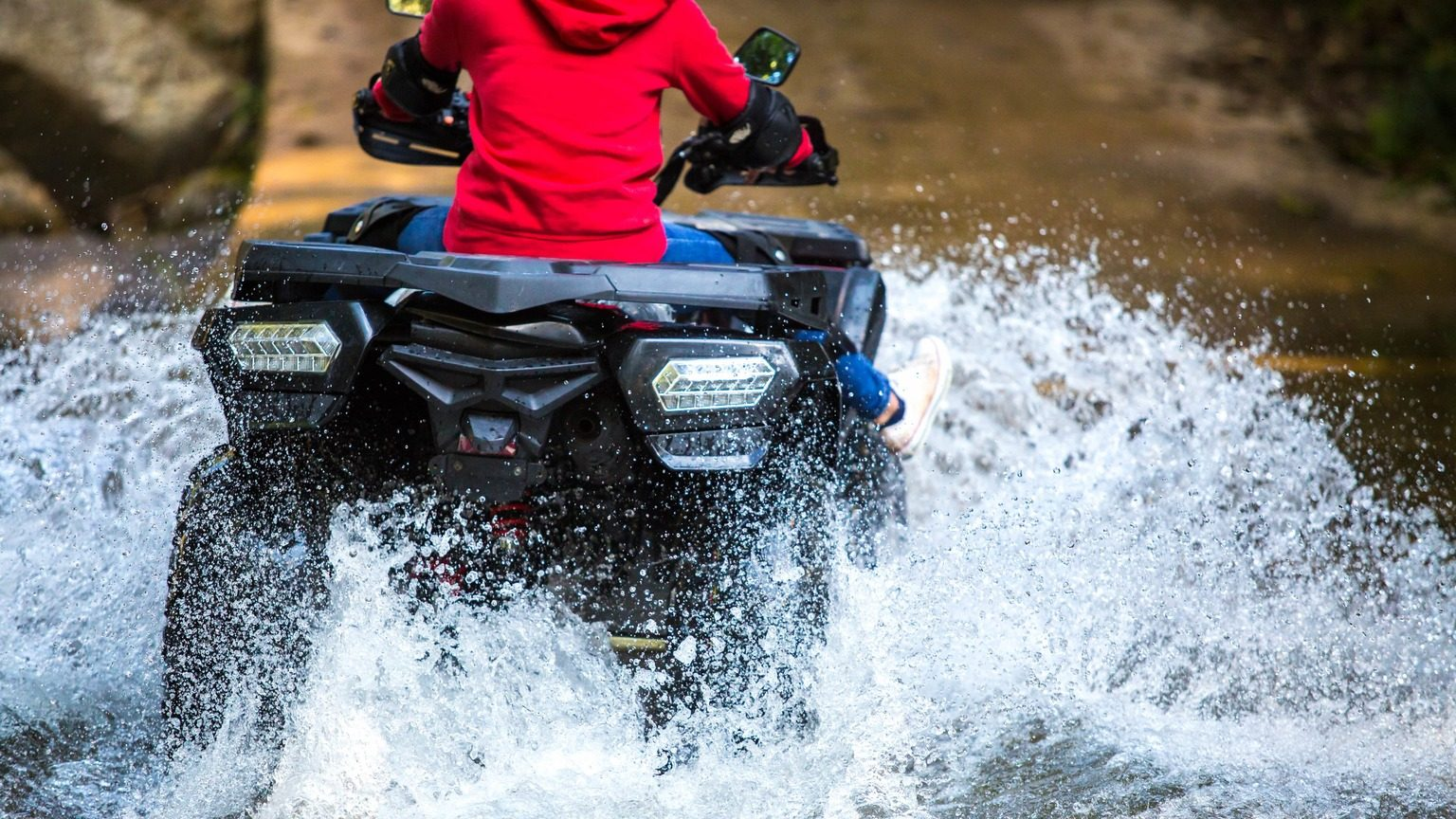 Driving an ATV through a shallow river