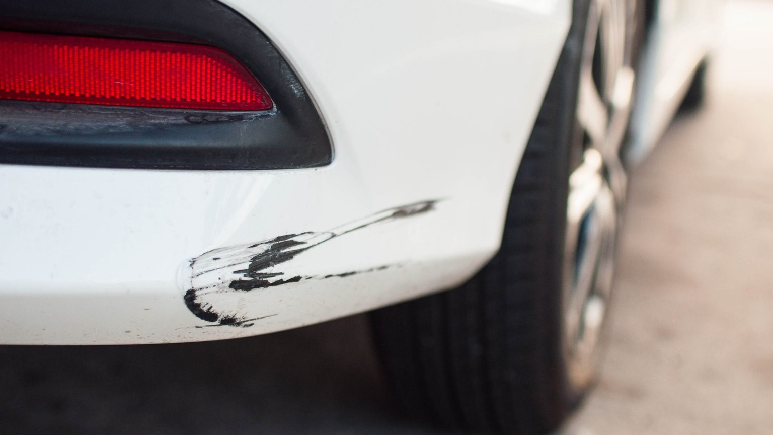 Scratched paint on the bumper of a white car