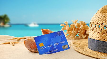 Credit card in the sand rested against a sea shell with ocean in the background