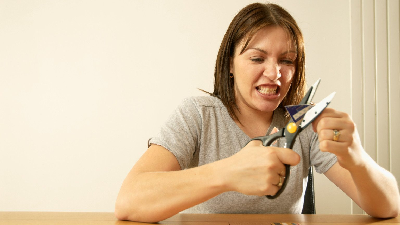 A woman angrily cutting up her credit cards