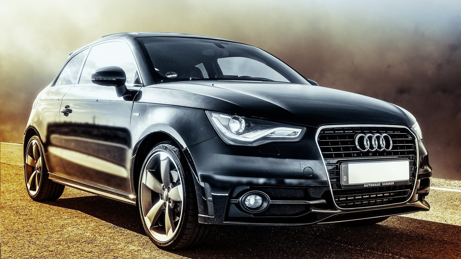 A black Audi sedan driving on a misty road
