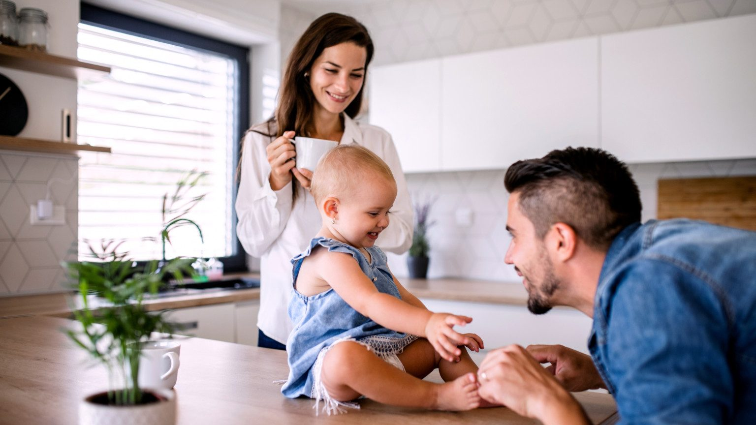Young parents with smiling baby in kitchen