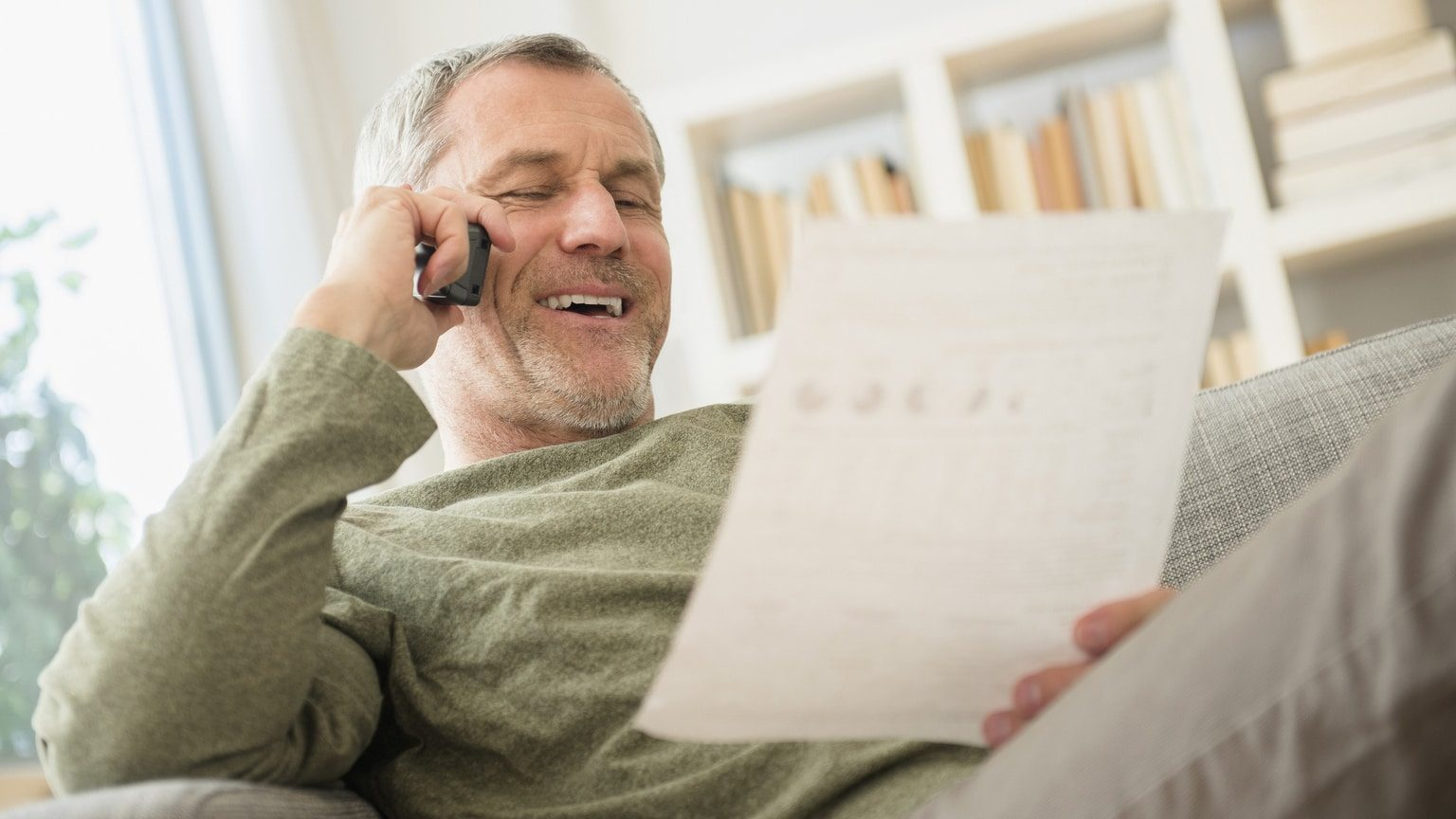 Man phoning car dealership to discuss his vehicle loan