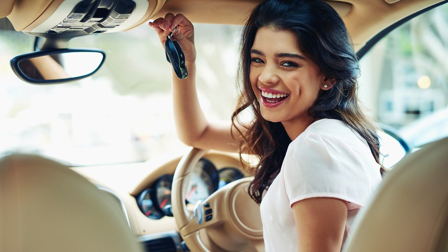 Young woman smiling while sitting in her new car