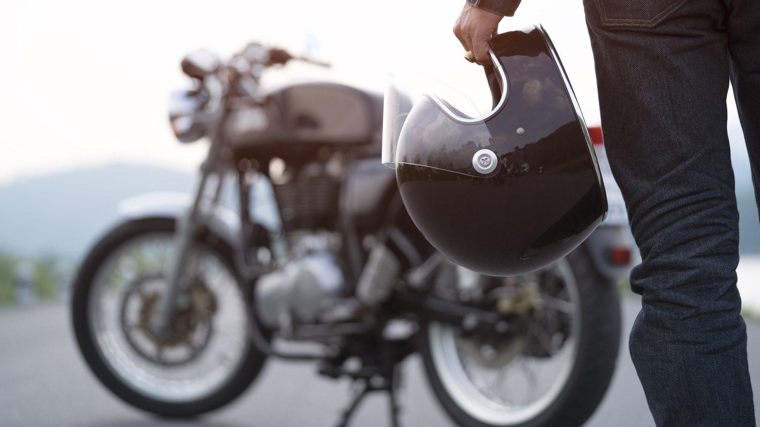 Man Holding Helmet Looking At Motorcycle