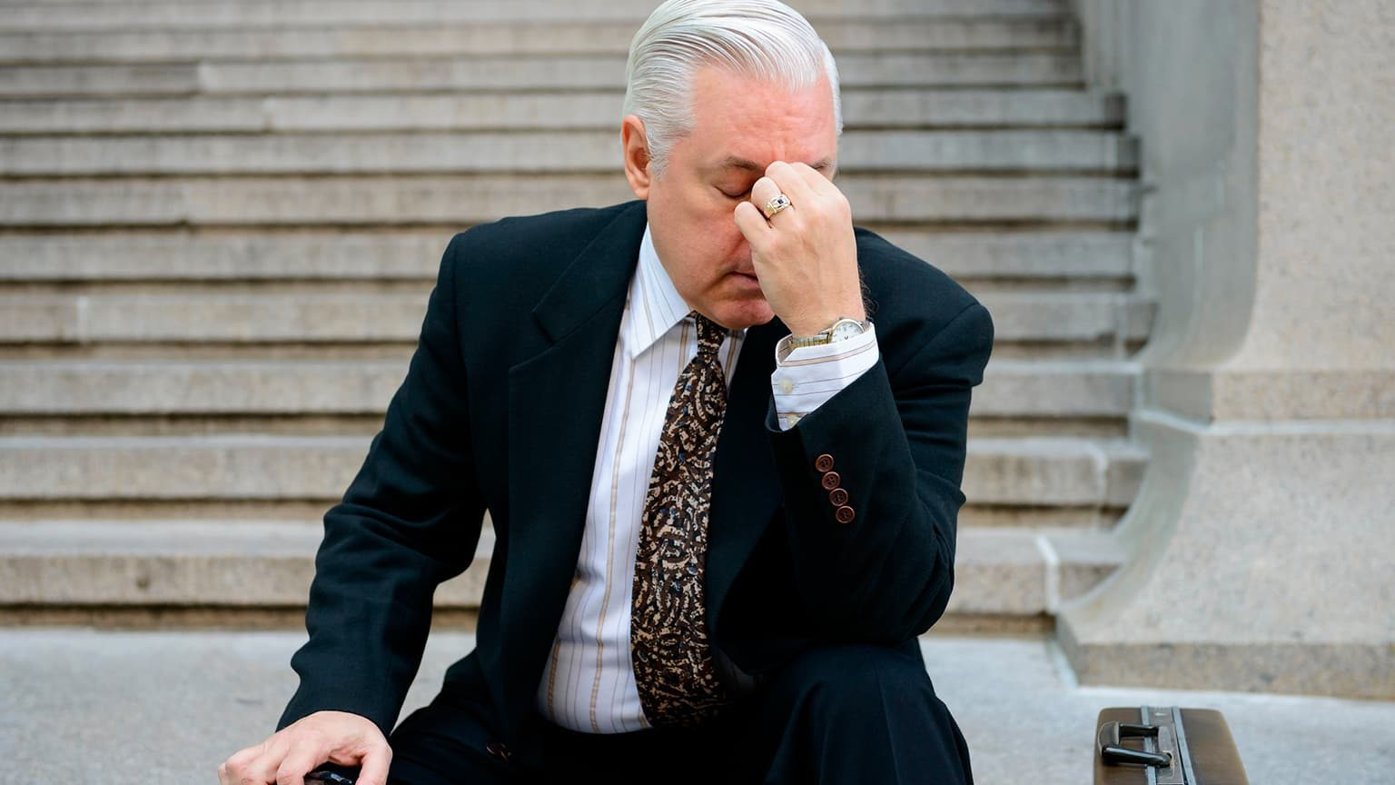 Older business man showing frustration while sitting on steps