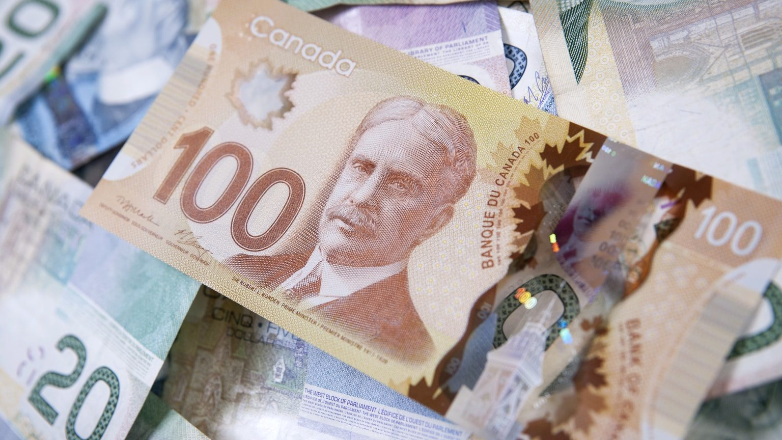 One hundred dollar bill on pile of Canadian money